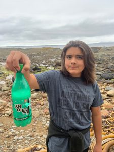 Boy holds up plastic bottle collected from the shoreline.