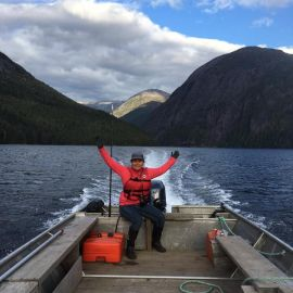 Spirit Bear Lodge guide on skiff raises both arms in the Great Bear Rainforest