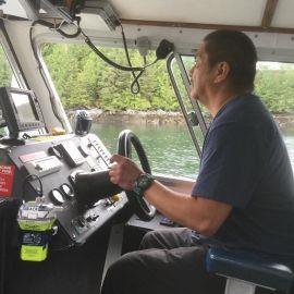 Spirit Bear Lodge boat captain drives crew boat in the Great Bear Rainforest